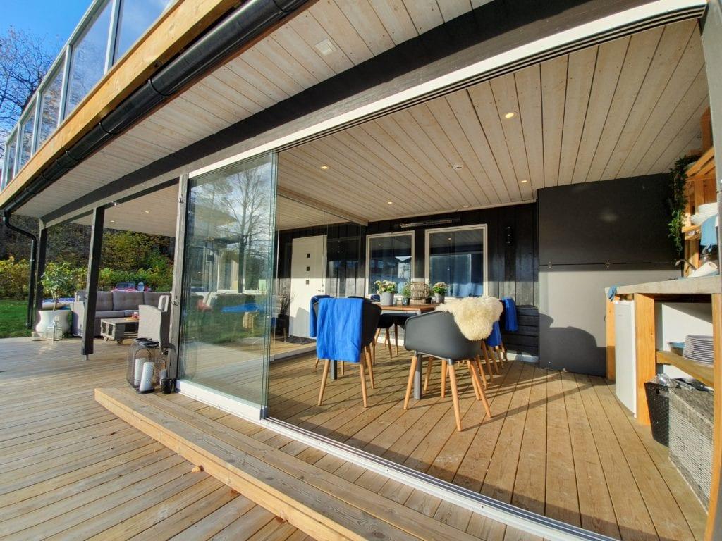 Her vises et innredet areal under terrassen, med utekjøkken, spisegruppe og innglassing
